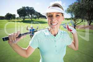 Lady golfer smiling at camera with partner cheering behind