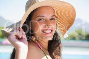 Beautiful brunette sitting by pool wearing straw sunhat