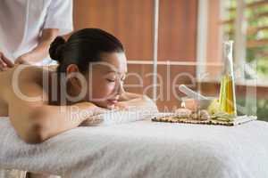 Brunette enjoying a massage with beauty treatments beside