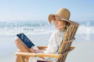 Smiling blonde sitting on wooden deck chair by the sea using tab