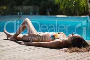 Slim brunette in bikini lying poolside
