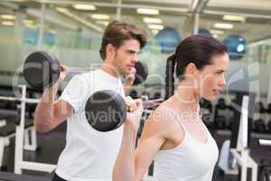 Fit couple lifting barbells together
