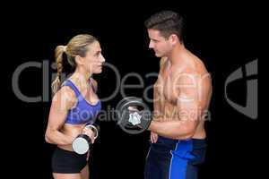 Crossfit couple posing with dumbbells