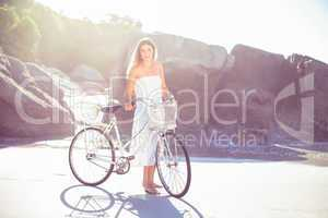 Beautiful blonde in white sundress standing with bike on the bea