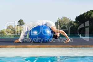 Peaceful brunette in cobra pose over exercise ball poolside