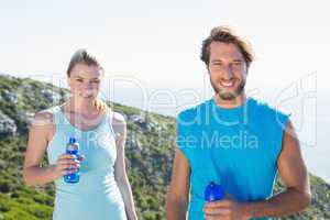 Fit couple standing at summit smiling at camera