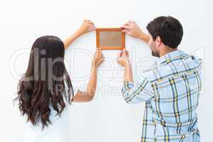 Happy young couple putting up picture frame