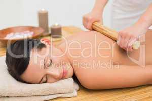 Beautiful brunette enjoying a bamboo roller massage