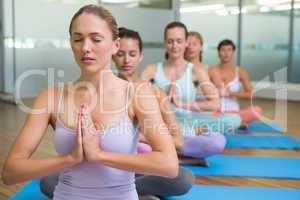 Yoga class in lotus pose in fitness studio