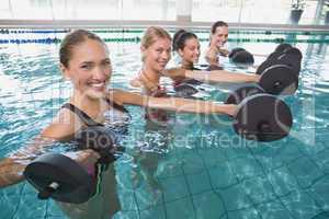 Smiling female fitness class doing aqua aerobics with foam dumbb