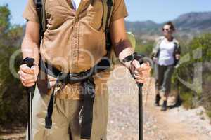 Hiking couple walking on mountain trail with poles