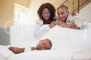 Baby boy sleeping peacefully on couch watched by parents