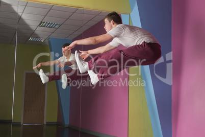 Cool break dancer mid air doing the splits in front of mirror