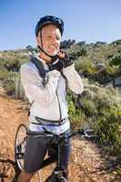 Fit cyclist adjusting helmet strap on country terrain smiling at
