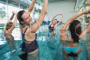 Female fitness class doing aqua aerobics on exercise bikes