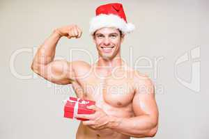 Portrait of shirtless macho man in santa hat holding gift