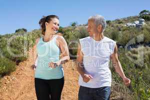 Fit smiling couple jogging down mountain trail
