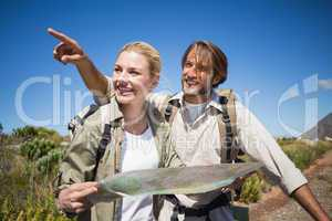 Hiking couple walking on mountain terrain looking at map