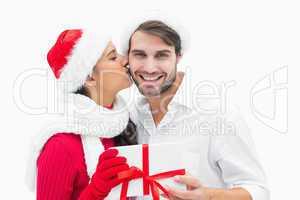 Attractive festive woman giving boyfriend a kiss and present