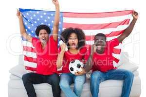 Cheering football fans in red sitting on couch with usa flag