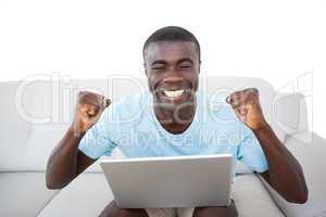 Cheering man sitting on couch using laptop