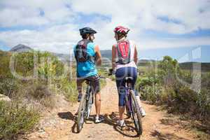 Fit couple about to cycle on mountain trail