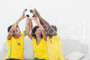 Brazil football fans sitting on couch holding ball