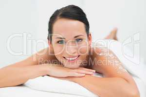 Peaceful brunette smiling at camera with salt scrub on back