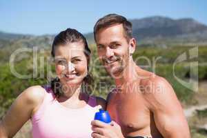 Active couple smiling at camera in the countryside