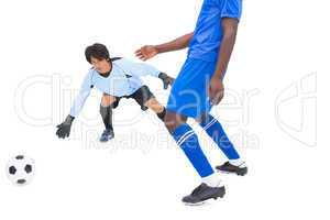 Football player in blue striking at keeper
