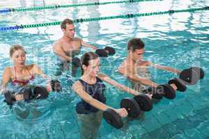Happy fitness class doing aqua aerobics with foam dumbbells