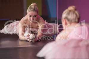 Graceful ballerina warming up in front of mirror