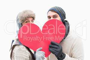 Attractive young couple in warm clothes holding red heart
