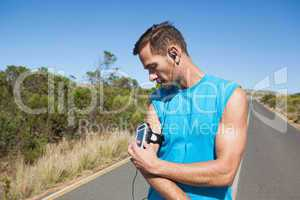 Athletic man adjusting his music player on a run