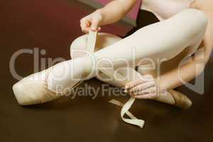 Ballerina tying the ribbon on her ballet slippers