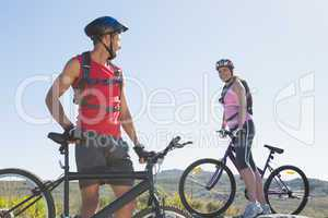 Fit cyclist couple standing at the summit smiling at each other