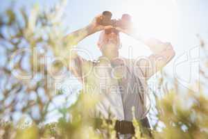 Hiker standing on country trail looking through binoculars