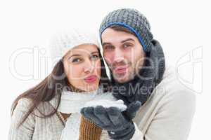 Attractive young couple in warm clothes blowing