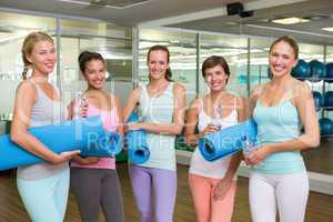 Smiling women in fitness studio before yoga class