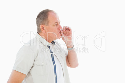 Older man holding hand to mouth for silence