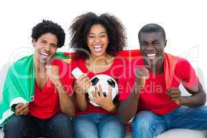 Cheering football fans in red sitting on couch with portugal fla
