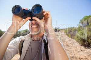 Hiker looking through his binoculars on country trail