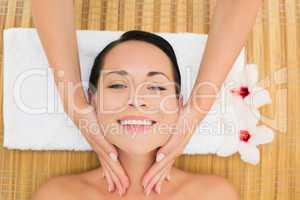 Smiling brunette enjoying a facial massage