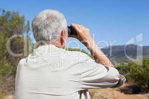 Hiker taking a break on country trail looking through binoculars