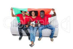 Portugal football fans in red on the sofa