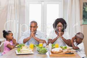 Happy family saying grace before meal