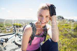 Fit pretty cyclist taking a break on rocky peak smiling at camer
