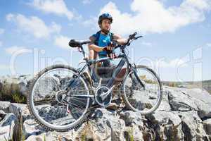 Fit cyclist taking a break on rocky peak