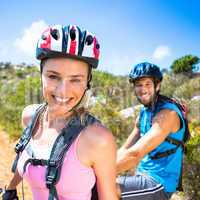 Fit couple cycling up mountain trail smiling