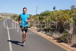 Athletic man jogging on open road